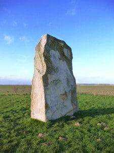une des faces du menhir de Lécluse au milieu d'un champs