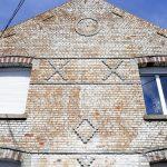 façade de maion avec des signes runiques, cercle, losange, croix et calice