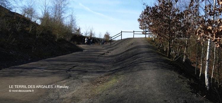 Chemin et promeneurs qui montent à flanc du terril des Argales de Rieulay